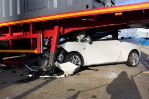 A car that has crashed into a lorry trailer causing much damage